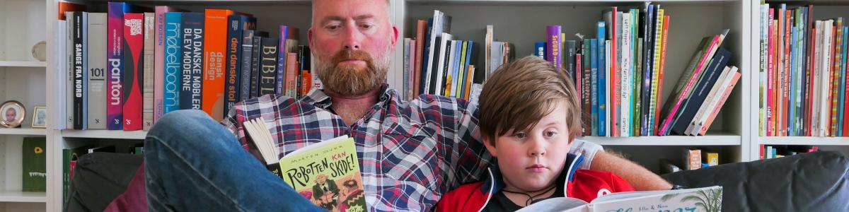 En mand og en dreng sidder i en sofa og læser