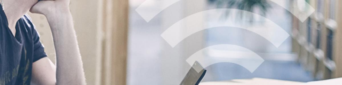 Billede af biblioteksbruger med computer og et WiFi logo på billedet