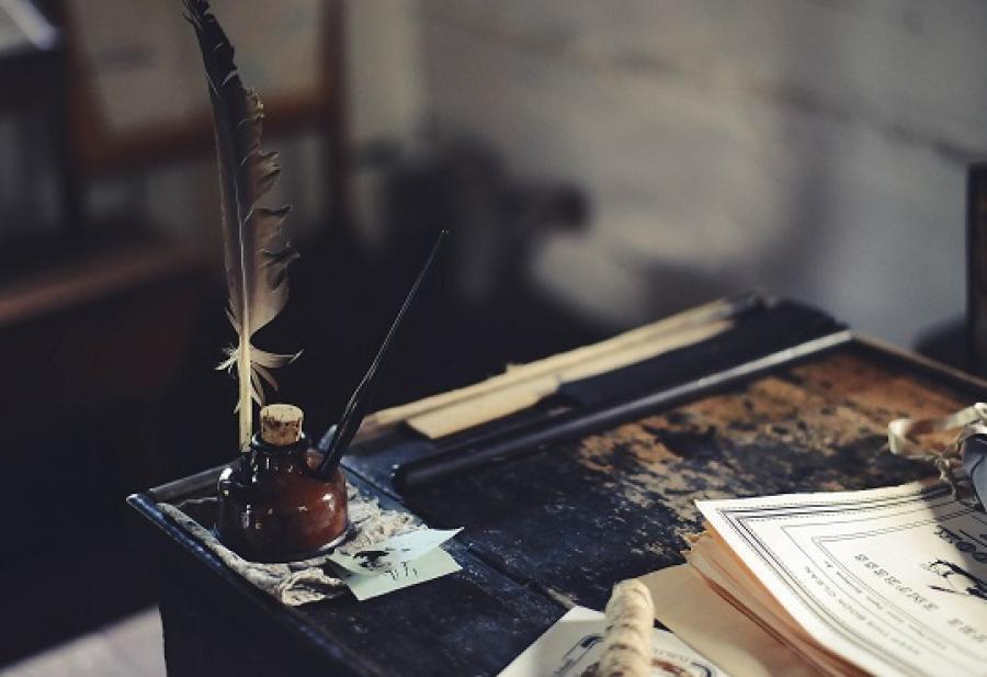 Billede af et skrivebord med blækhus og fjerpen