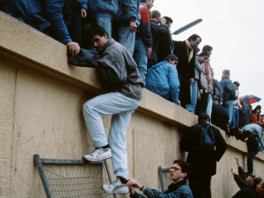 Foto af mennesker der kravler over Berlinmuren