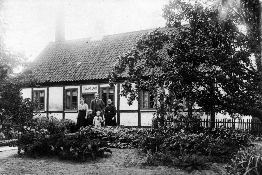 Gammelt sort-hvidt foto af 5 personer foran bindingsværkshus