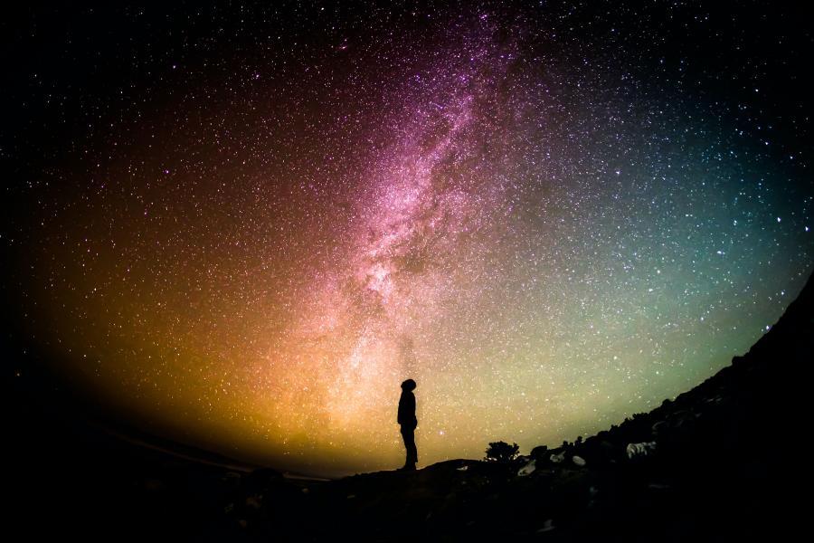 Et menneske står i silhouet og kigger op på en farverig stjernehimmel.