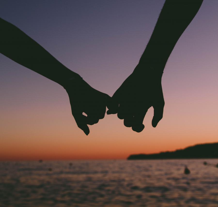 Romantisk billede at hænder der holder hinanden i krog med lillefingeren