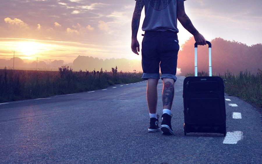 Billede af en mand der går på landevejen med en kuffert